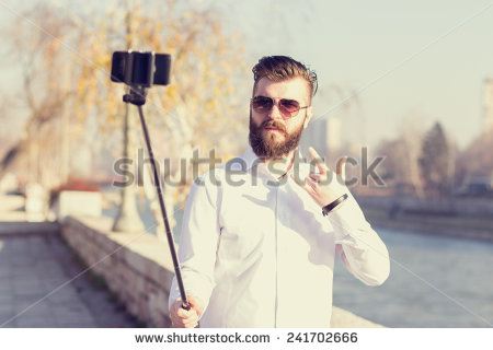 """Hipster style bearded man taking selfie with selfie stick."" - actual description from Shutterstock. Click to see full copyright details and purchase a high-res non-watermarked version, if that's really your bag."